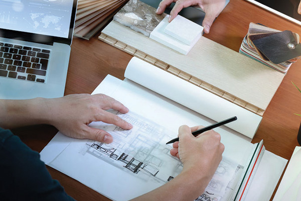 A person drafting up a sketch of a building